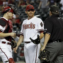 Arizona Diamondbacks' Ian Kennedy, middle, and Miguel Montero, left, talks with umpire Doug Eddings after the San Diego Padres scored a run in the first inning of a baseball game Tuesday, Sept. 18, 2012, in Phoenix.