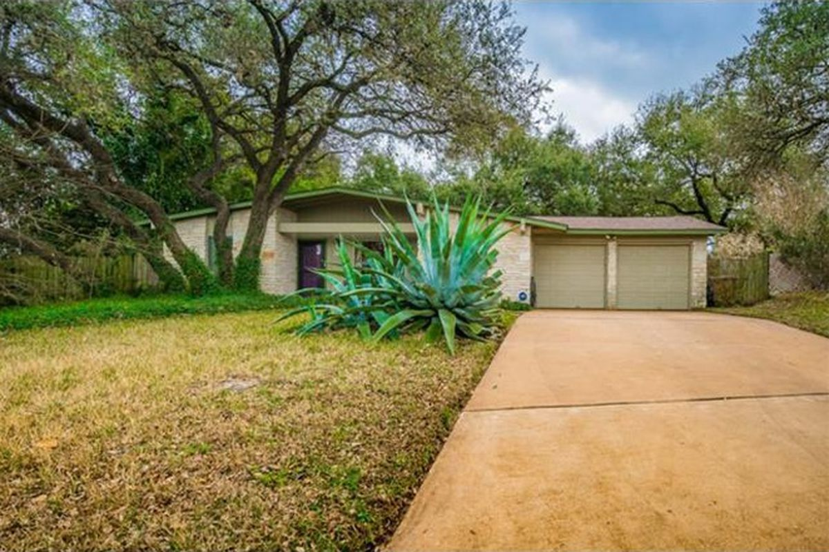 1960s stone atomic ranch style house with light green trim and garage doors, big tree and yucca in front yard