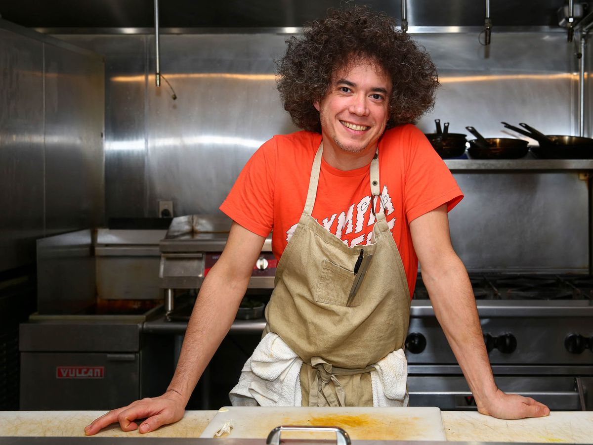 Eric Rivera (in a red shirt and tan apron) leans on a counter in his Addo kitchen.