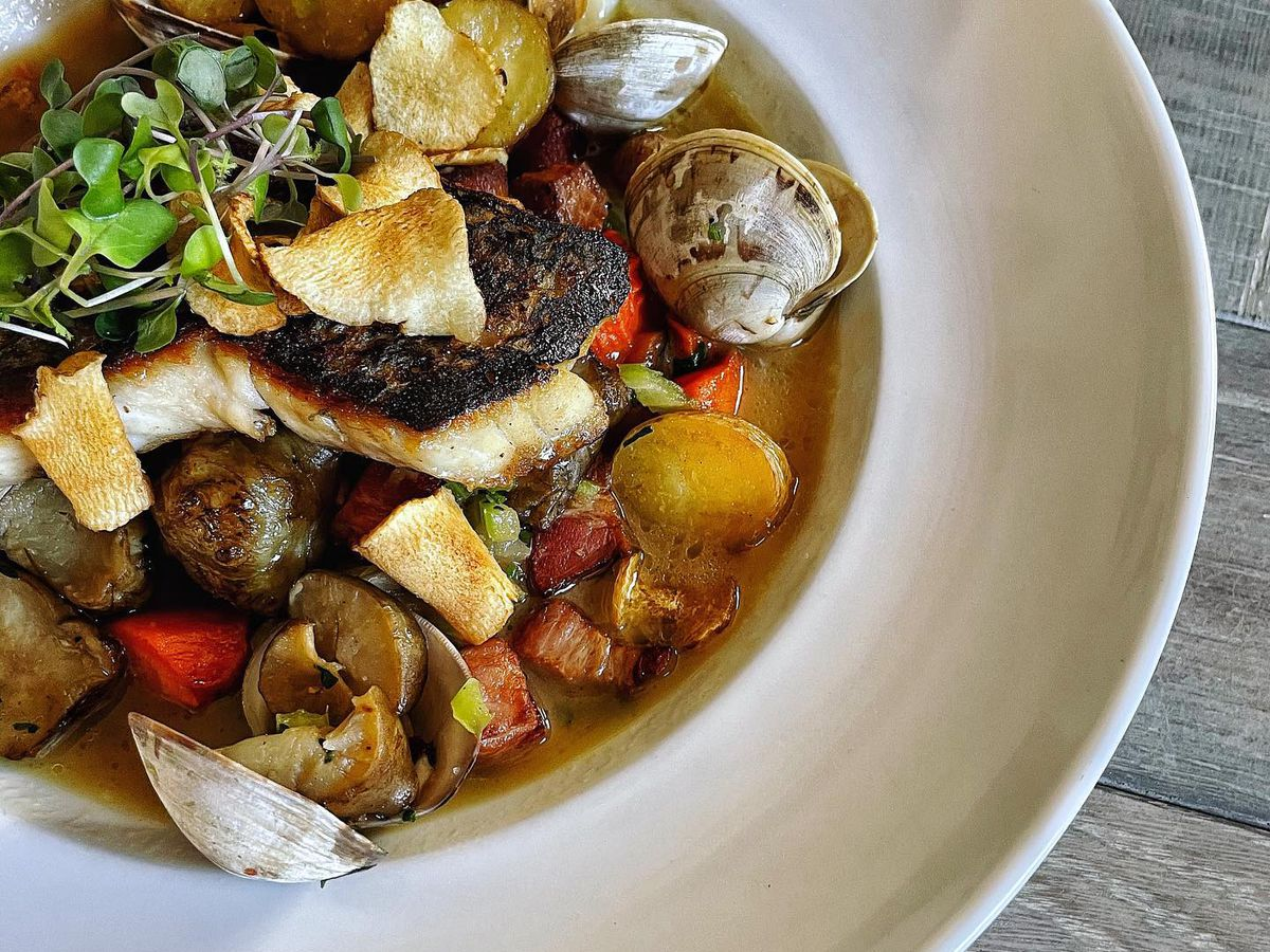 A bowl of chowder with clams, sunchokes, and potatoes garnished with herbs and sun-dried tomatoes from Table and Main in Roswell, GA