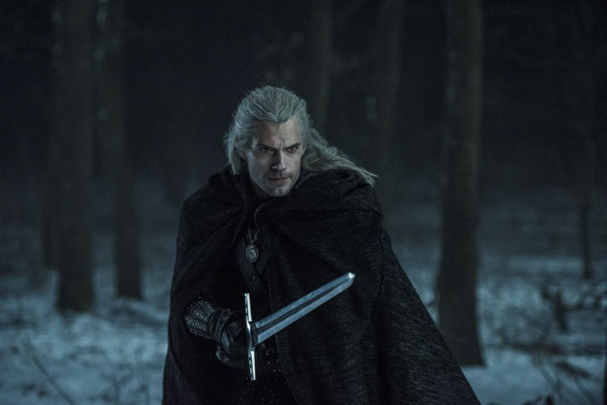 A man with long, white hair wields a sword.