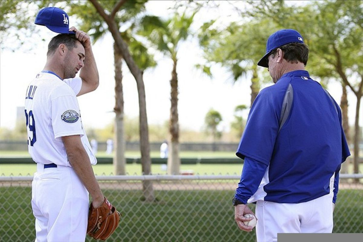 Feb 28, 2012; Glendale, AZ, USA; Los Angeles Dodgers starting pitcher Ted Lilly (left) and pitching coach Rick Honeycutt during a bullpen session during a workout at Camelback Ranch.  Mandatory Credit: Jake Roth-US PRESSWIRE