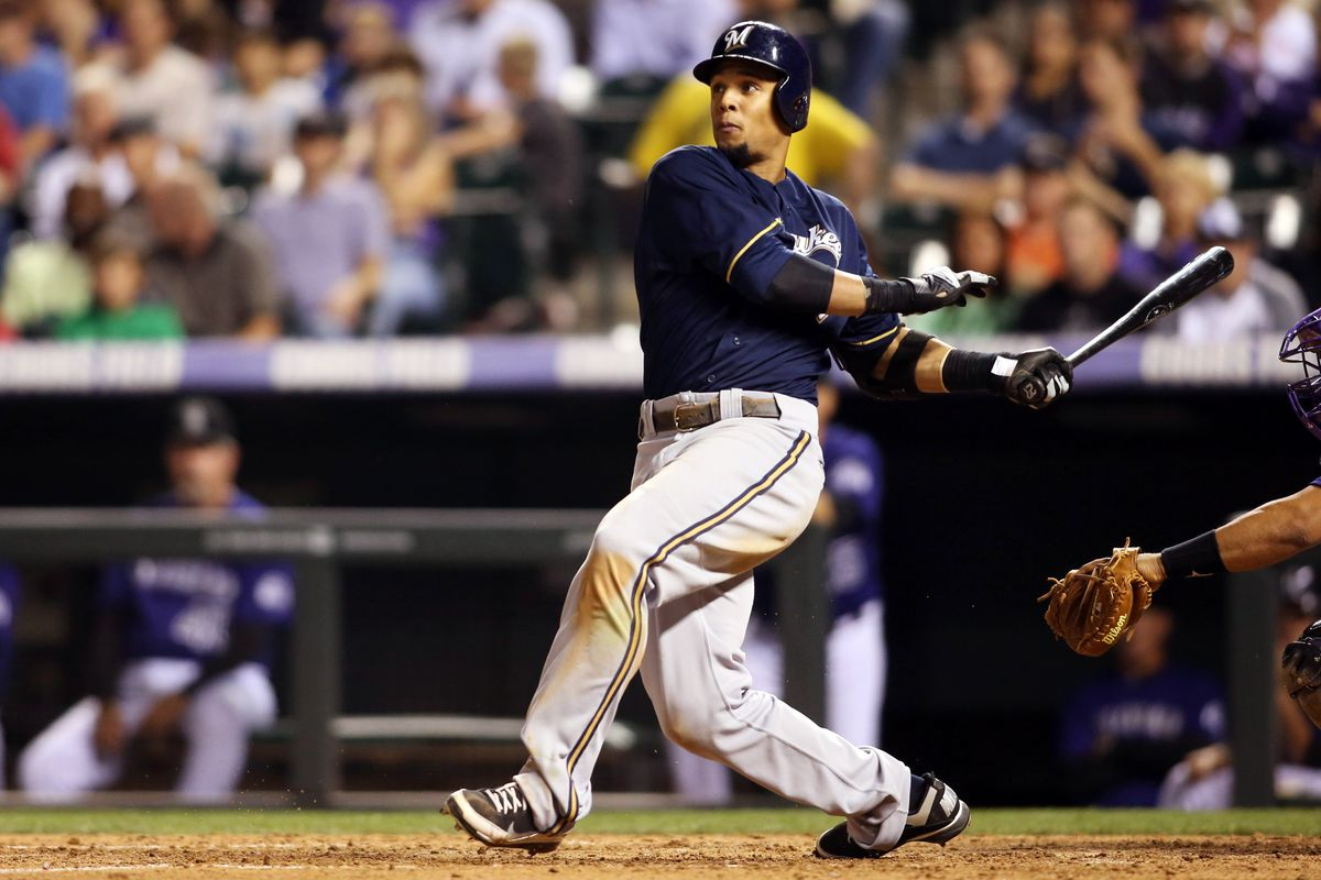 Denver, CO, USA; Milwaukee Brewers center fielder Carlos Gomez (27) hits a home run during the sixth inning against the Colorado Rockies at Coors Field.  Mandatory Credit: Chris Humphreys-US PRESSWIRE