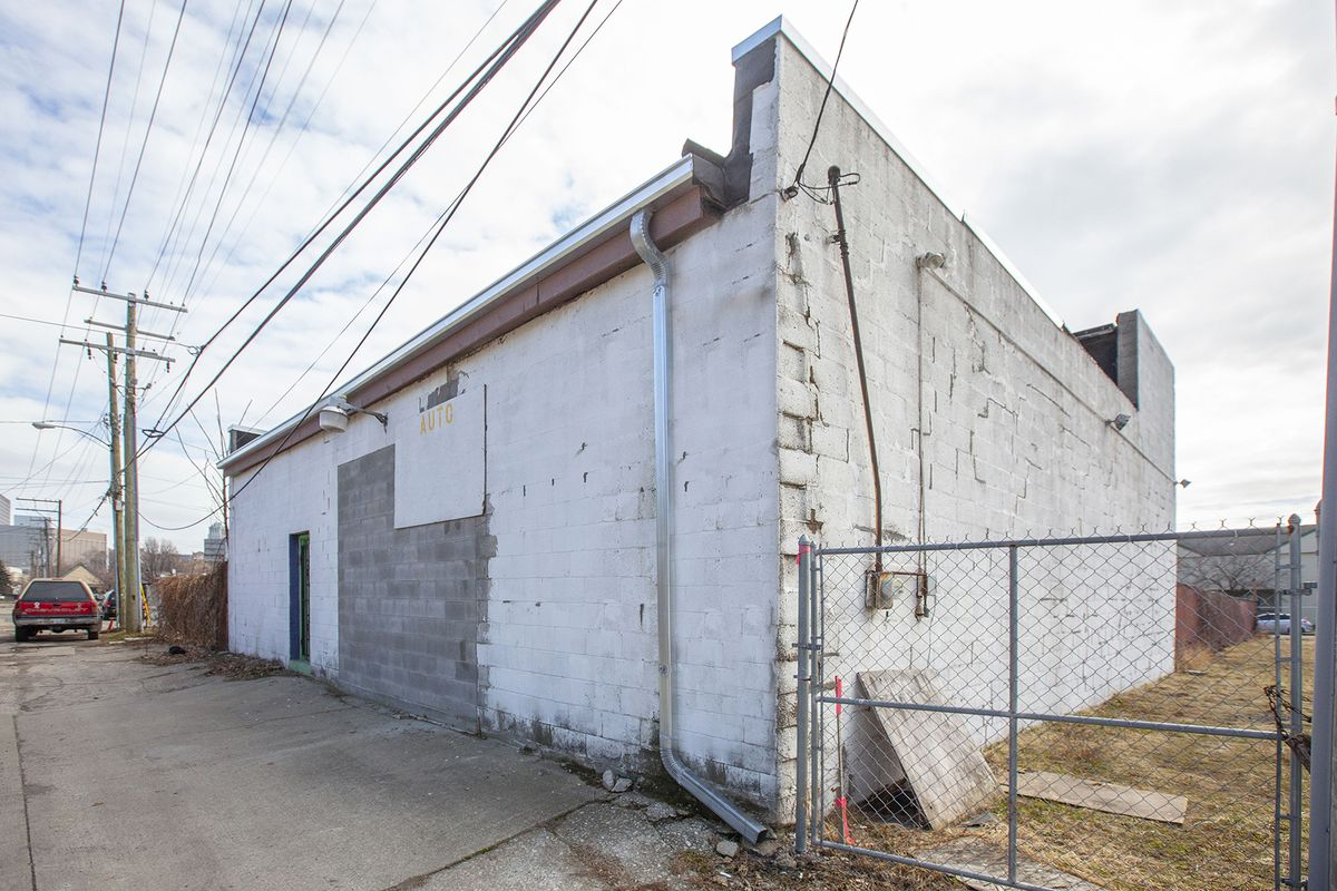 The outside of the building is made of white-painted cinder block.