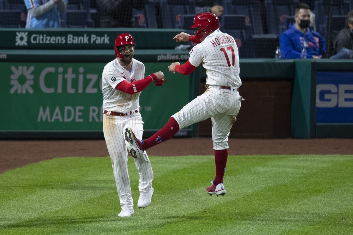 Bryce Harper #3 and Rhys Hoskins #17 of the Philadelphia Phillies celebrate after both scored a run in the bottom of the eighth inning against the New York Mets at Citizens Bank Park on April 5, 2021 in Philadelphia, Pennsylvania.