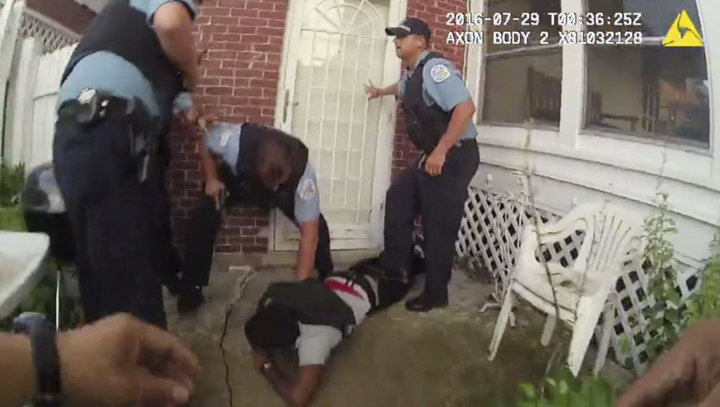 In this frame grab from a body-camera video provided by the Independent Police Review Authority, Chicago police officers handcuff Paul O'Neal, suspected of stealing a car, after they fired into the vehicle he was driving and then pursued him through a yar