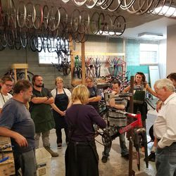 A group observes a bicycle mechanic working on a bike at the Ogden Bicycle Collective.