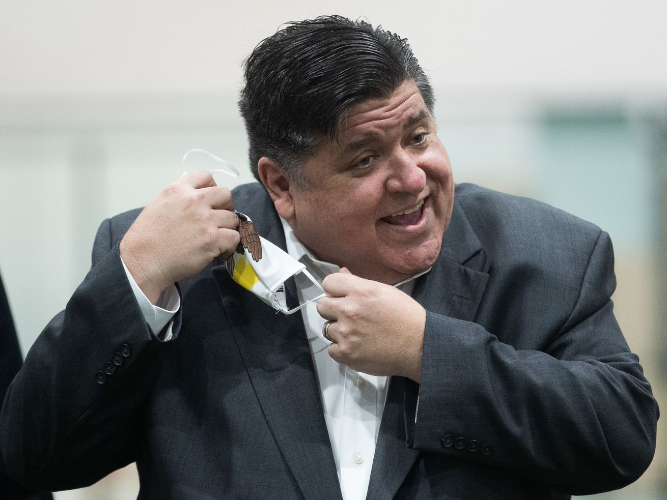 Gov. J.B. Pritzker takes off his mask before speaking to the media during an event in the Pullman neighborhood in October.