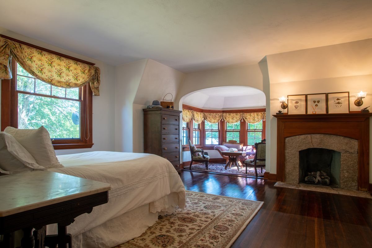 A bedroom features a white bed, fireplace, wooden floors, and a reading nook.