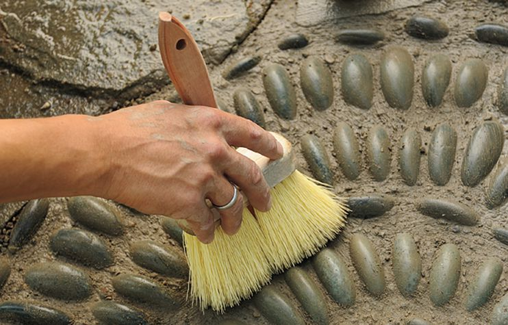 Person Brushes Pebble Mosaic After Saturating And Shaping The Mix