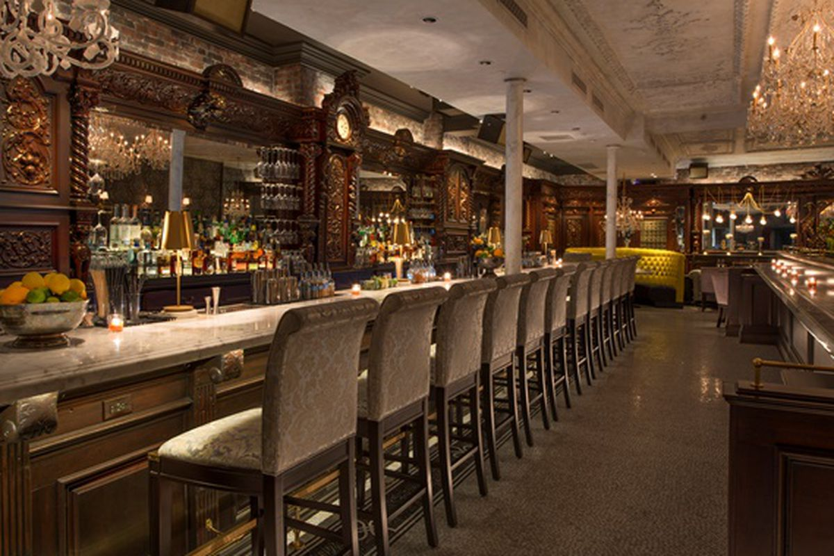 Wide angle of a restaurant with a marble bar, plush seating, and elaborate wall decor