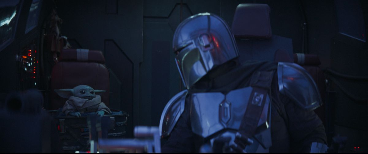 The Mandalorian looks back at Baby Yoda in the cockpit of the Razor Crest.