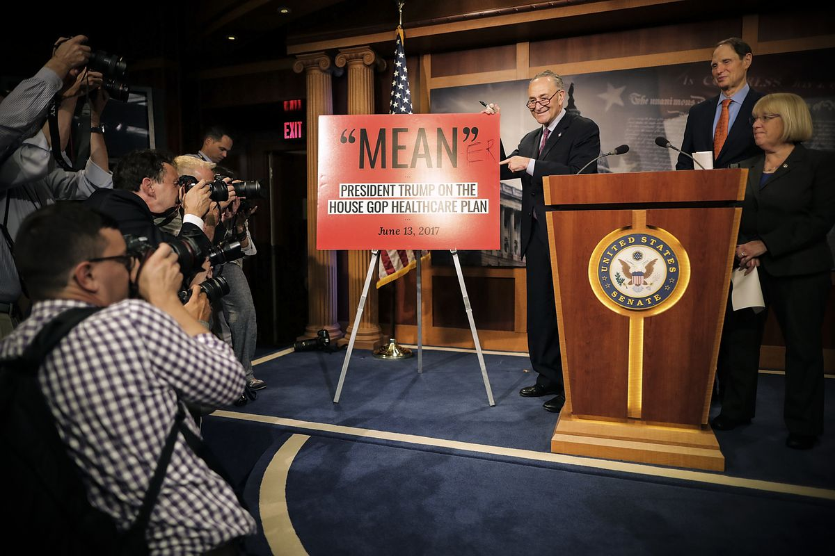 Senate Minority Leader Charles Schumer (D-NY) poses for photographers after altering a poster with President Trump's description of the House version of Obamacare reform during a news conference on June 22, 2017 in Washington, DC.