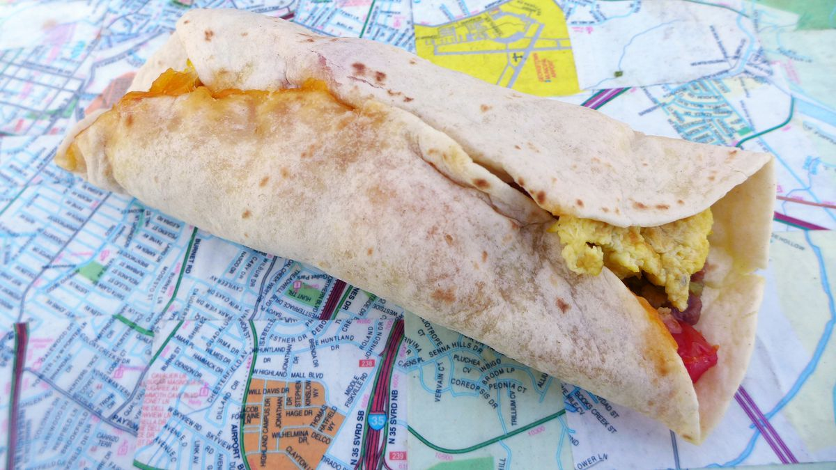 A flour tortilla rolled taco on top of a highway map.