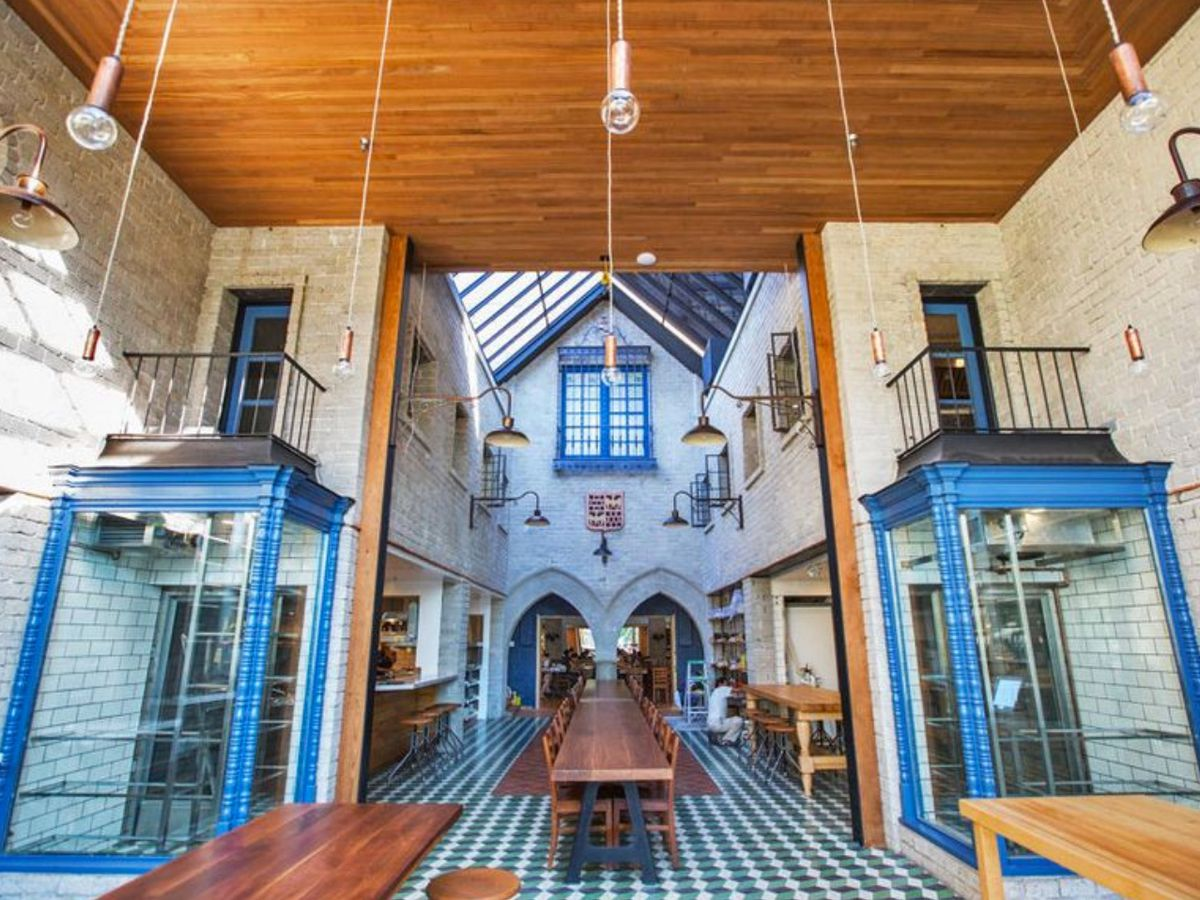 A tall, gothic-looking restaurant with colorful tile and long wooden tables.