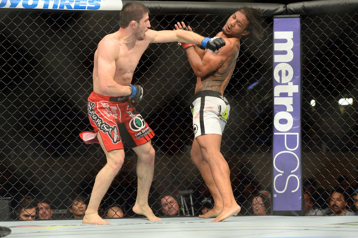 Rustam Khabilov (L) punches Ben Henderson.