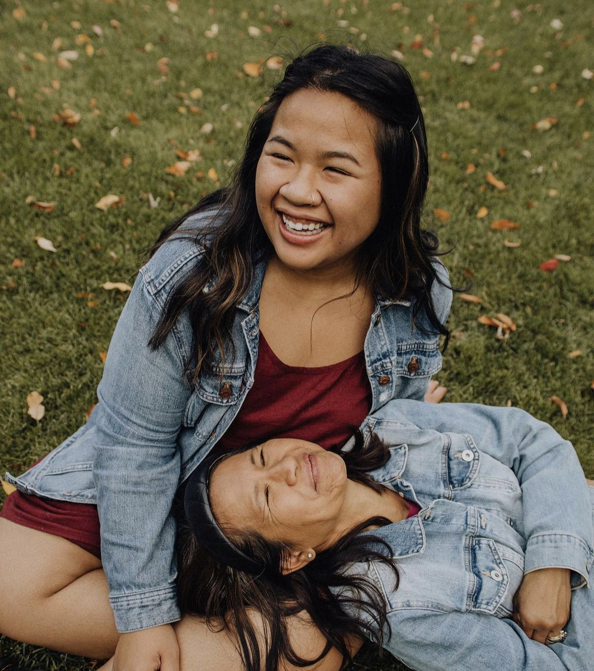 Two smiling women leaning up against each other while sitting on the grass