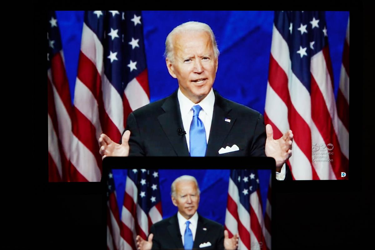 A photo of three screens, each smaller than the other, showing Biden — in a dark suit and blue tie, his white pocket square folded into three points — speaking at a podium in front of US flags. The largest screen is a TV; the medium screen, just below it, is a tablet, and the smallest, below that, is a phone. All three are glowing in a dark room.