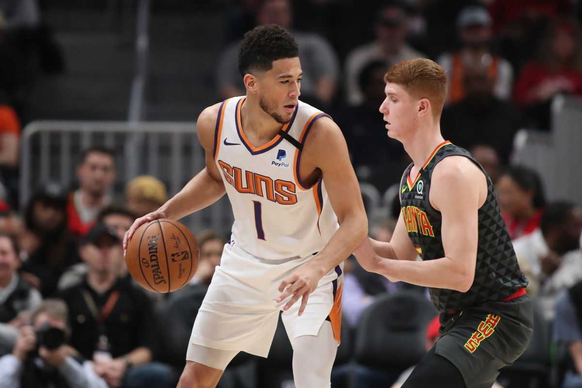 Phoenix Suns guard Devin Booker controls the ball against Atlanta Hawks guard Kevin Huerter in the first quarter at State Farm Arena