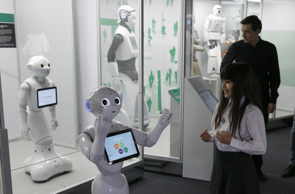Charllotte Abbot reacts to the movement of Pepper, an interactive French-Japanese robot, during a press preview for the Robots exhibition held at the Science Museum in London, Tuesday, Feb. 7, 2017. (AP Photo/Alastair Grant)