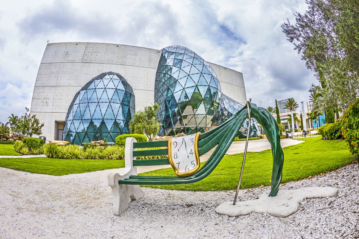 The exterior of the Salvador Dali Museum in Florida. The facade is white and there are two large glass structures shaped like bubbles in front. In the foreground is a curved bench with a melting clock on it.