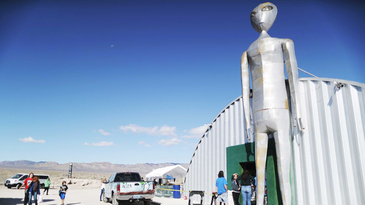 A giant metal sculpture of an alien stands outside a trailer in the desert.