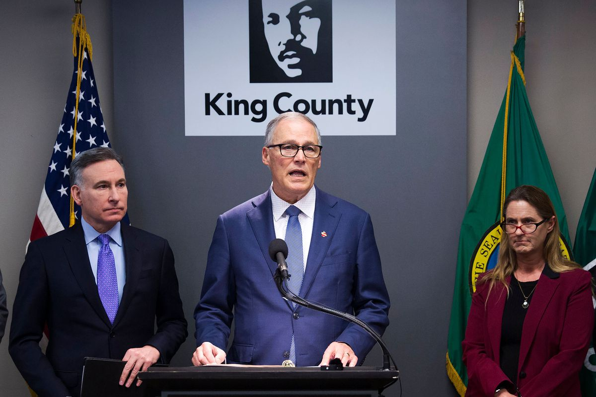 Inslee speaks flanked by public health officials in King County.