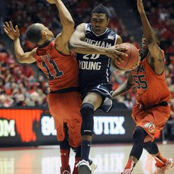 Brigham Young Cougars guard Frank Bartley IV (24) draws the foul from Utah Utes guard Brandon Taylor (11) while driving to the basket during a game at the Jon M. Huntsman Center on Saturday, Dec. 14, 2013.