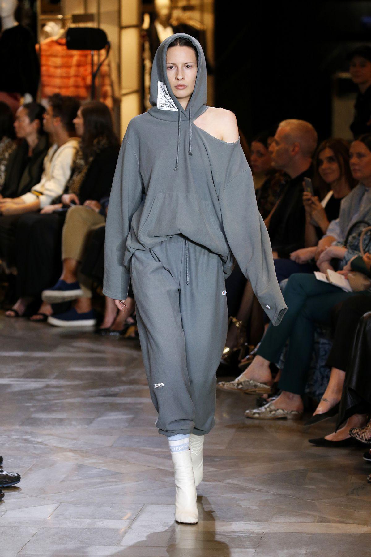 Model walks runway wearing Vetements x Champion gray outfit
