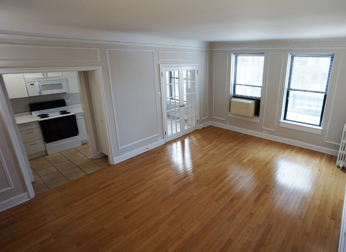 A view of the living room and kitchen. There are large windows, hardwood, and French doors which go to the eat-in area.