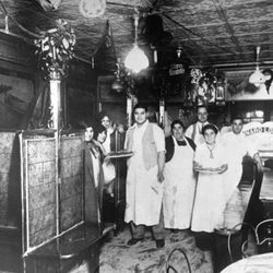 """In the original Lombardi's, circa1925 (left to right): Giovanni Lombardi, Filomena Lombardi, Gennaro Lombardi (back row), and George Lombardi (other two men to the right and people in the booth to the left, not identified)<span class=""""credit""""> <a href=""""ht"""