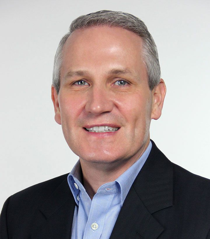 A grey haired man smiling.