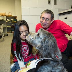 A girl reads to Bogee and his animal therapy handler Larry Hiller as part of Intermountain Therapy Animal's READ program in Duluth, Georgia.