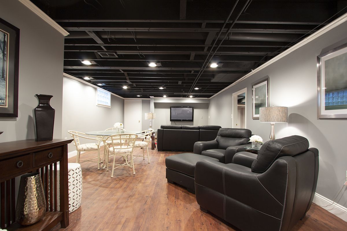 A long room with gray walls, black sofas and chars, and a flat-screen TV.