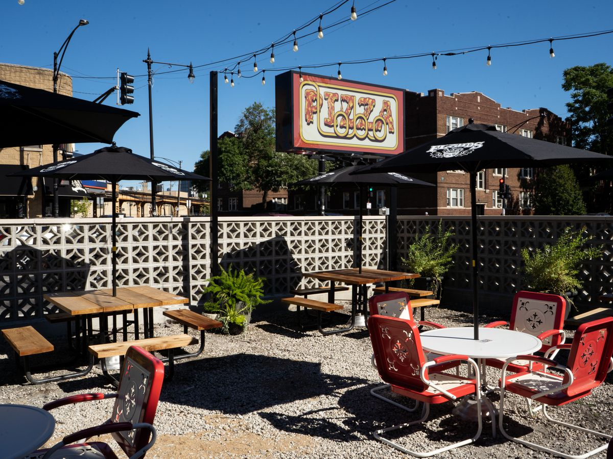 """A walled-off outdoor patio with round and square tables. A sign reads """"Pizza Lobo."""""""