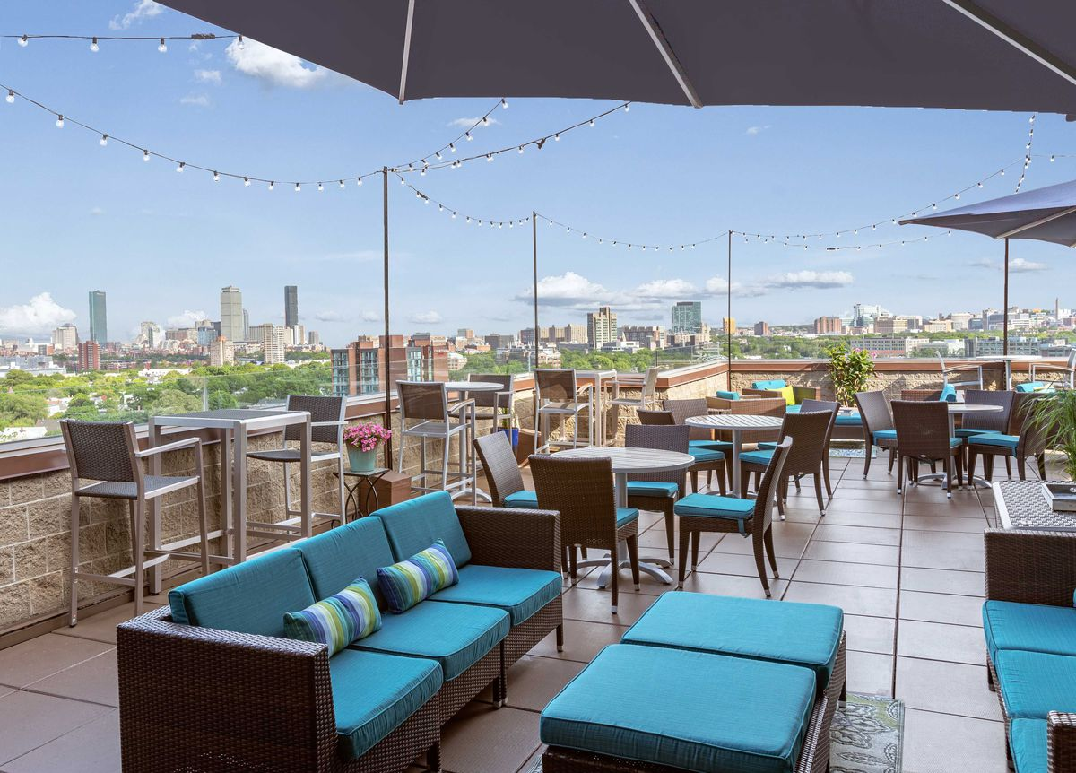 Daytime view of a rooftop bar, featuring outdoor lounge furniture in a teal and dark brown color scheme. Skyline views are visible over the edge of the roof.