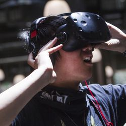 """Conan Zhang, co-founder and CEO of the virtual reality startup business Grace Foundry experiences his virtual reality world at the Lassonde Studios on the University of Utah campus in Salt Lake City on Friday, June 23, 2017. """"They provide us with great office spaces,"""" said Zhang. """"They also provide us with lawyers, accounting, funding and coffee!"""""""