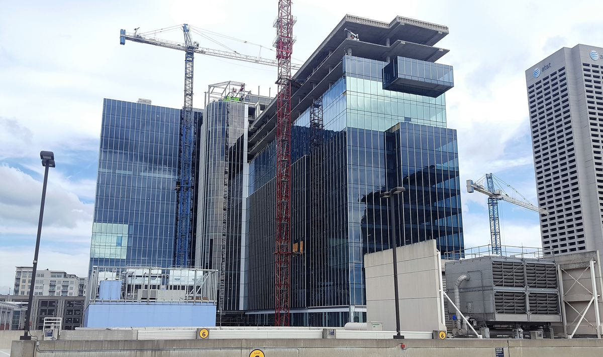 A glassy, blue, L-shaped office tower is under construction and surrounded by cranes.