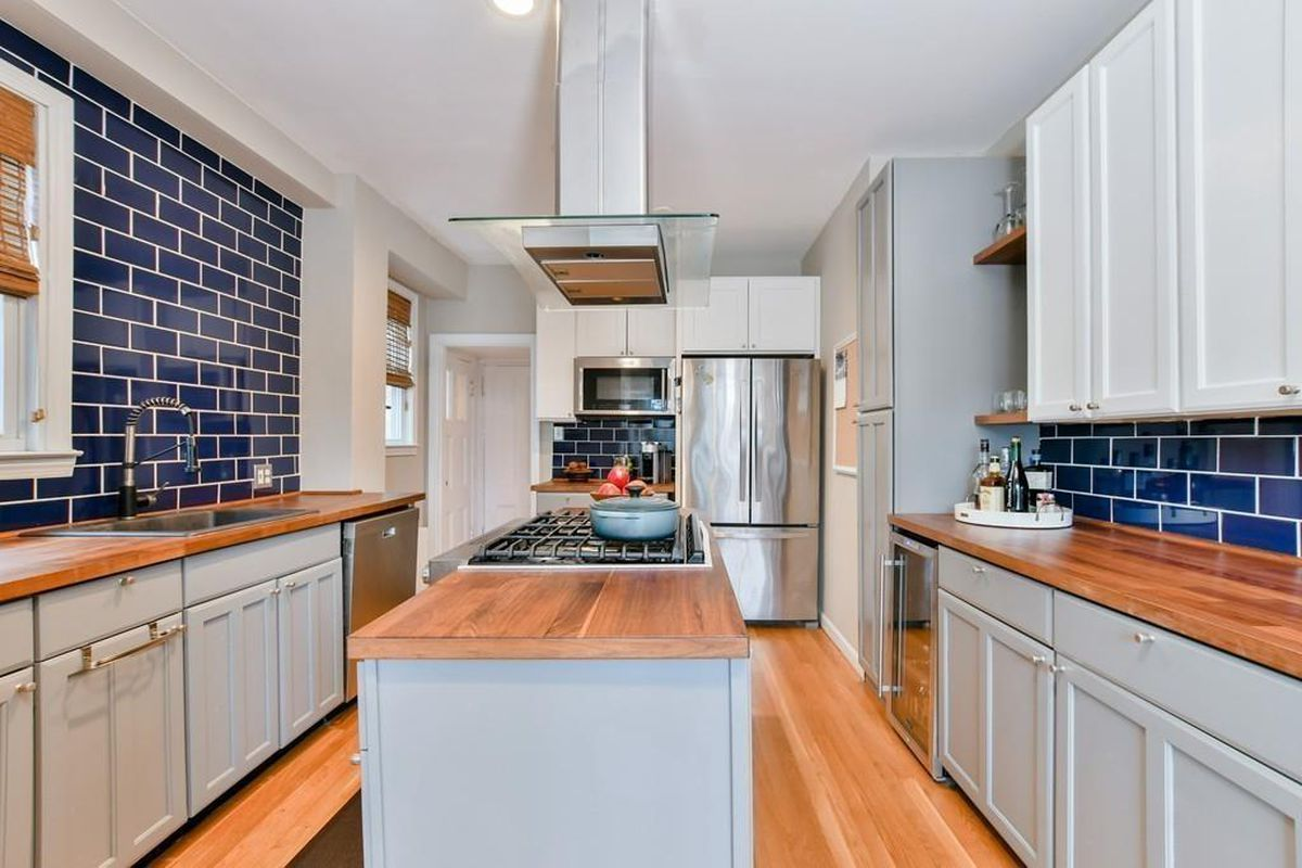 A kitchen with counters on either side and an island in the middle.