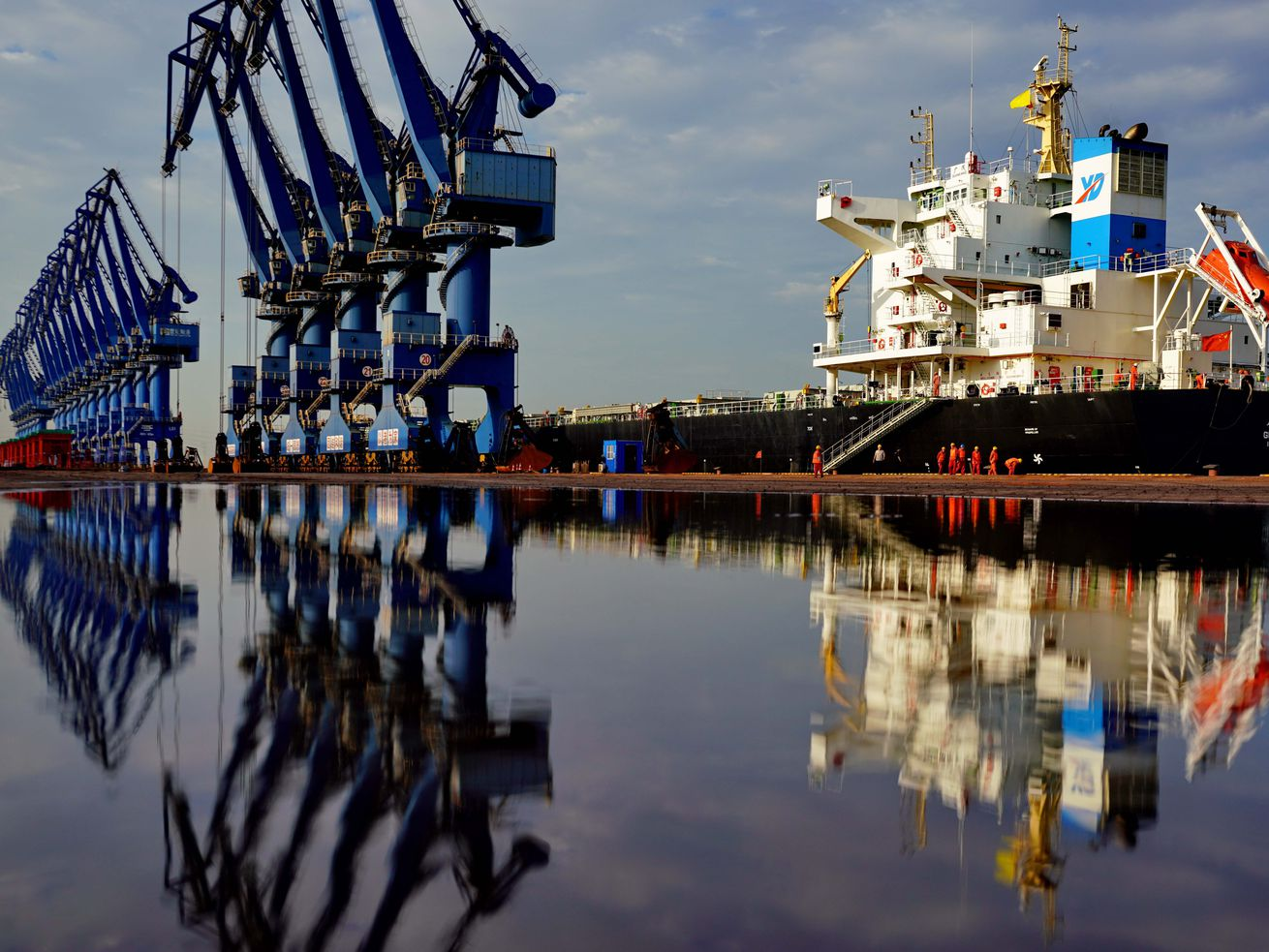 Blue cranes and a massive cargo ship are reflected in still water as the ship is loaded with goods. Workers in orange hurry across the wharf.