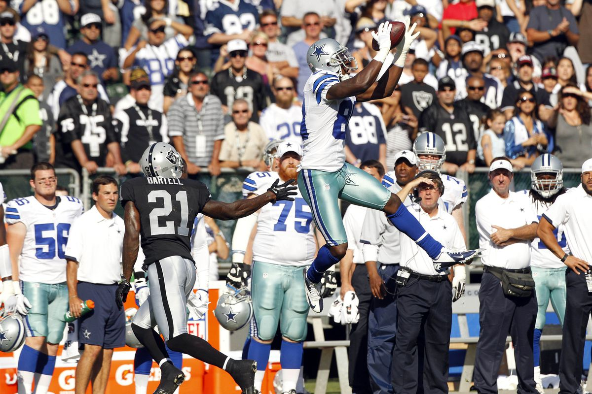 August 13, 2012; Oakland, CA, USA; Dallas Cowboys wide receiver Dez Bryant (88) makes a catch in front of Oakland Raiders defensive back Ron Bartell (21) in the first quarter at O.Co Coliseum. Mandatory Credit: Cary Edmondson-US PRESSWIRE