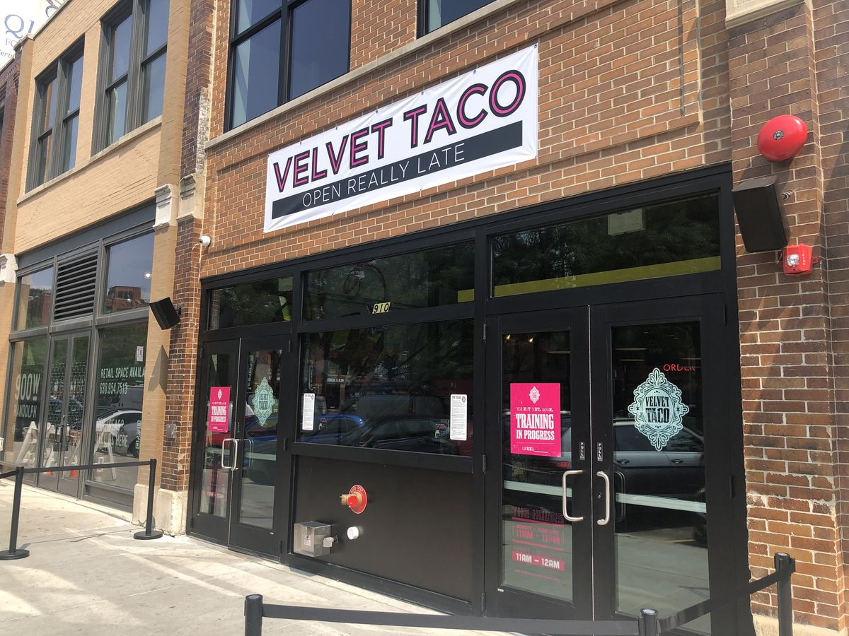 """A brick storefront with a temporary banner that reads """"Velvet Taco"""""""