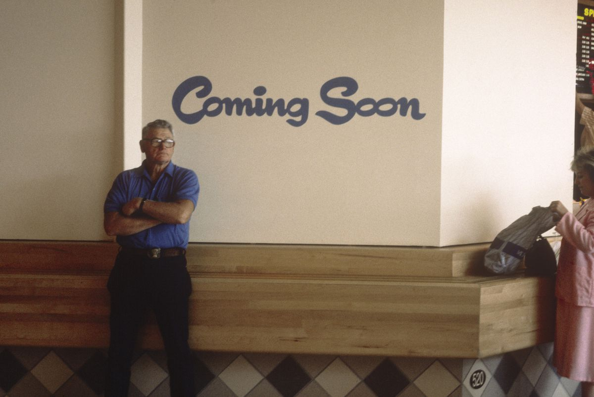 """A man inside a shopping mall in front of a """"coming soon"""" sign."""