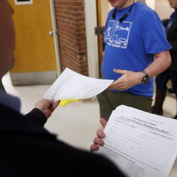 Caucus volunteer Brendan Smith passes out provisional ballots to voters at a Democratic caucus at Emerson Elementary School in Salt Lake City on Tuesday, March 22, 2016. The location ran out of ballots and had to print more on site.