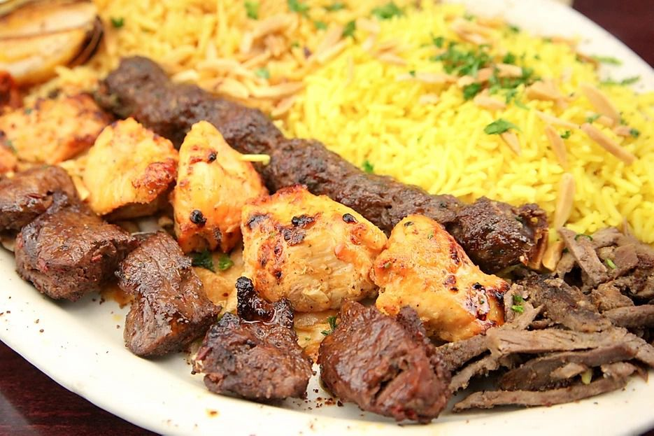 A plate of grilled meats and rice.