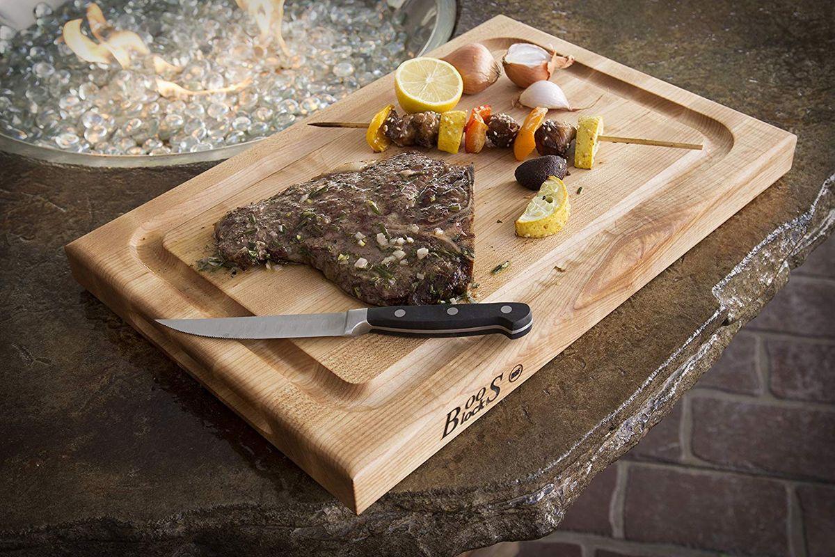 A steak, kabob, and knife on a cutting board