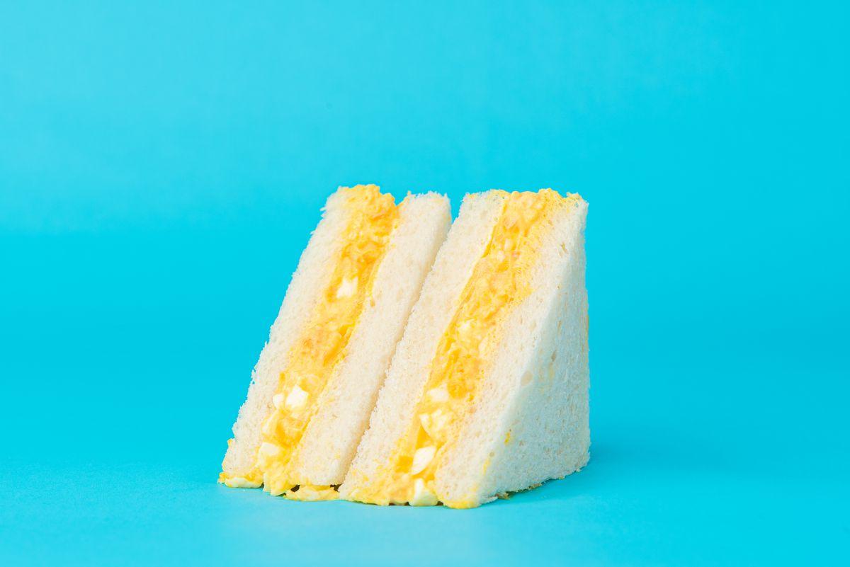 Egg salad sandwich on blue background.