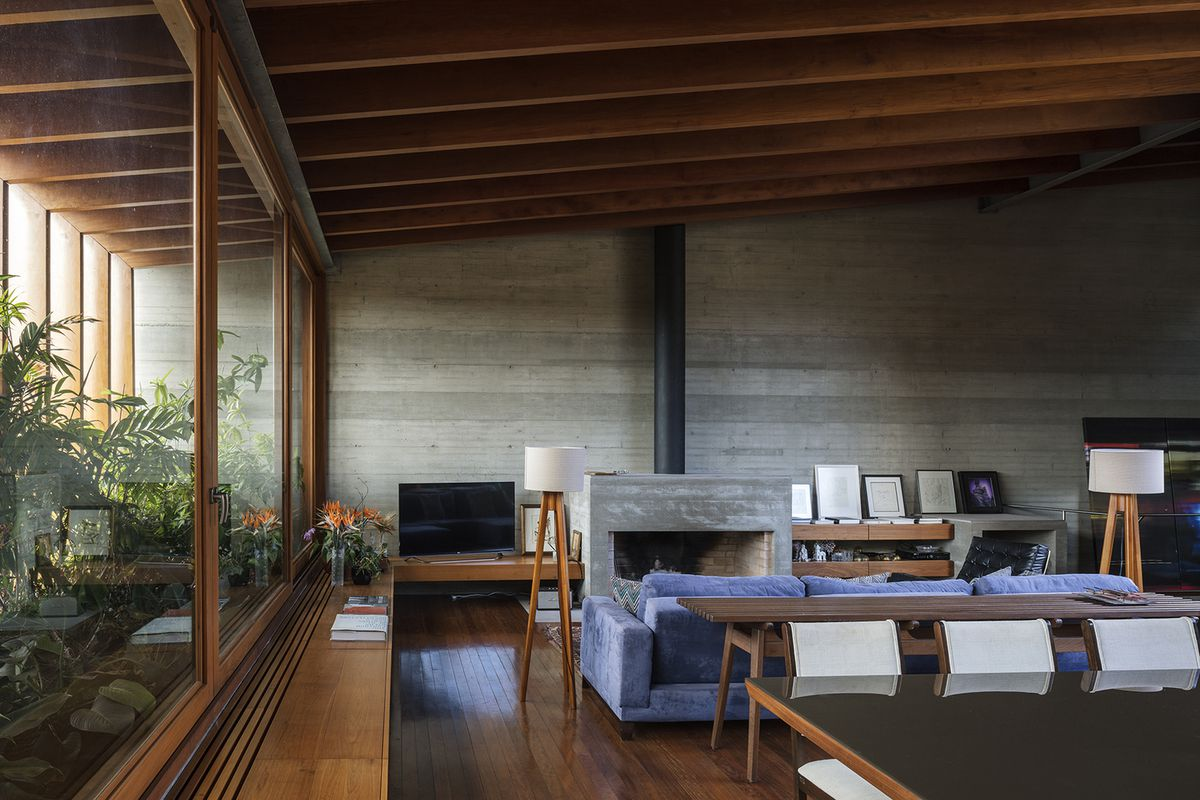 Living room with slanted timber ceiling, smooth gray walls, and wooden floors.