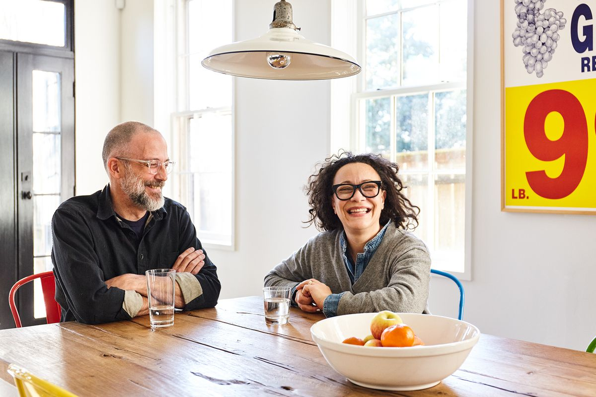The homeowners, a man and a woman, sit at a large wooden dining room table. There is a bowl of fruit on the table. There is a light fixture hanging over the table.