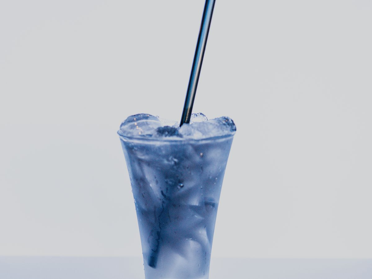 A bright blue cocktail in a glass with ice and a black straw
